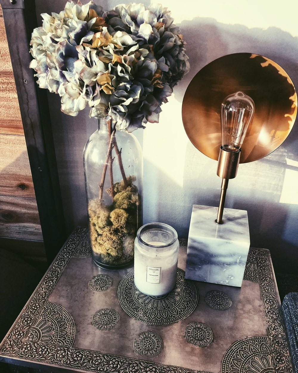 Rustic home decor bedside table with faux flowers, home fragrance, and Edison bulb lamp.