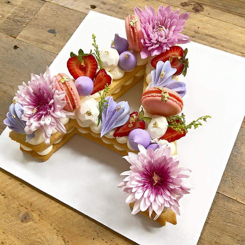 LETTER/ NUMBER TART CAKES - What a statement dessert! A definite show stopper that can be classy any fun! Two large almond cookie stacked in the letter or number of your choosing. Topped with macarons, meringues, fresh fruit, decorated in fresh flowers on top of a mascarpone whipped cream filling.