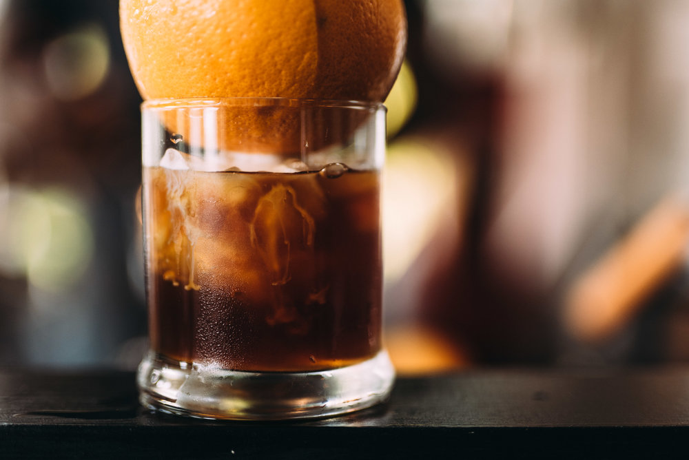 Gilbert    The Gilbert snatches it's influence from the most traditional cocktail roots. The Old Fashioned. The blend of fizzy citrus and smooth cold brew will melt you into an introspective daze. It may only be an 8oz drink, but it's full of subtle complexity and bold flavor. The fusion of sugars, bitters, and coffee make for a strong yet stimulating beverage. Definitely a man's man kind of drink. Sit down with a Gilbert and slip into some contemplative reflection.