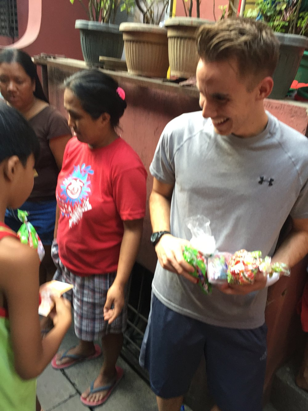 Volunteers making children smile by sharing Christmas candy.