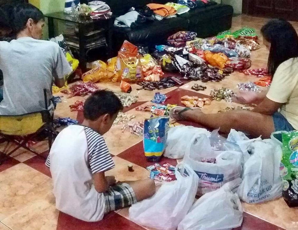 Volunteers preparing candies to distribute for the children