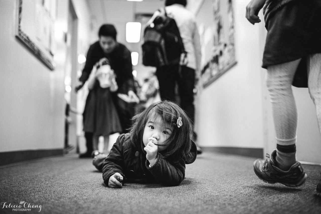 Tired girl in middle of school hallway | North Vancouver Family Photographer, Felicia Chang Photography