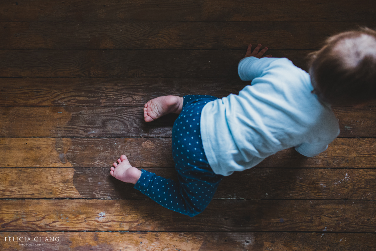 one year old girl crawling on hard wood floor