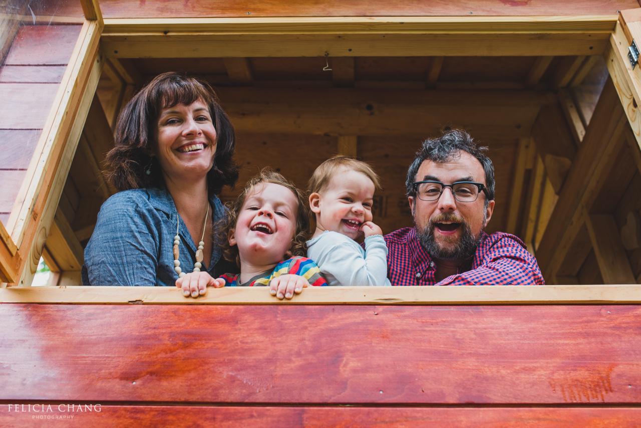family of four peeking through tree house window