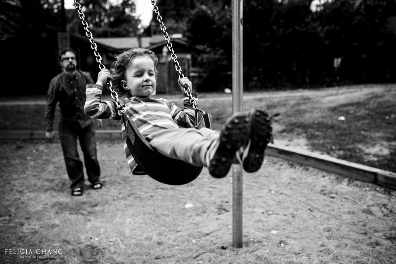 little boy enjoying the swing with eyes closed