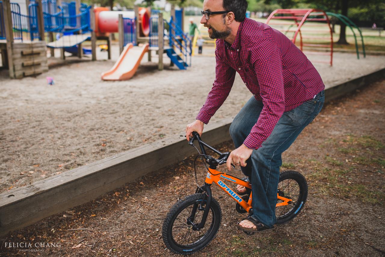 Dad riding son's bike around the playground