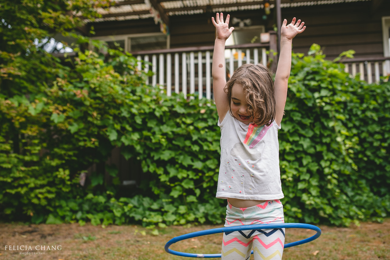 a girl with a Hoola hoop in the backyard