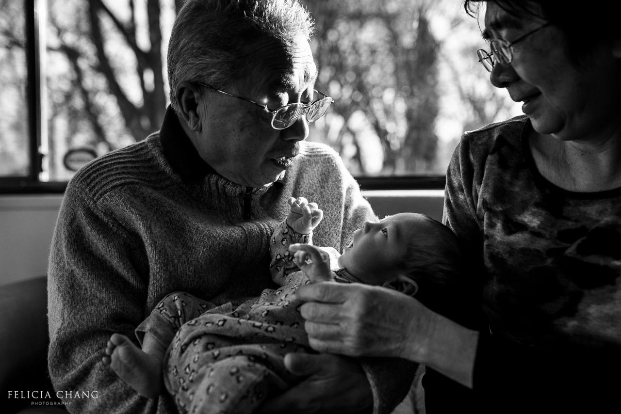 Grandparents cuddling with newborn grandson