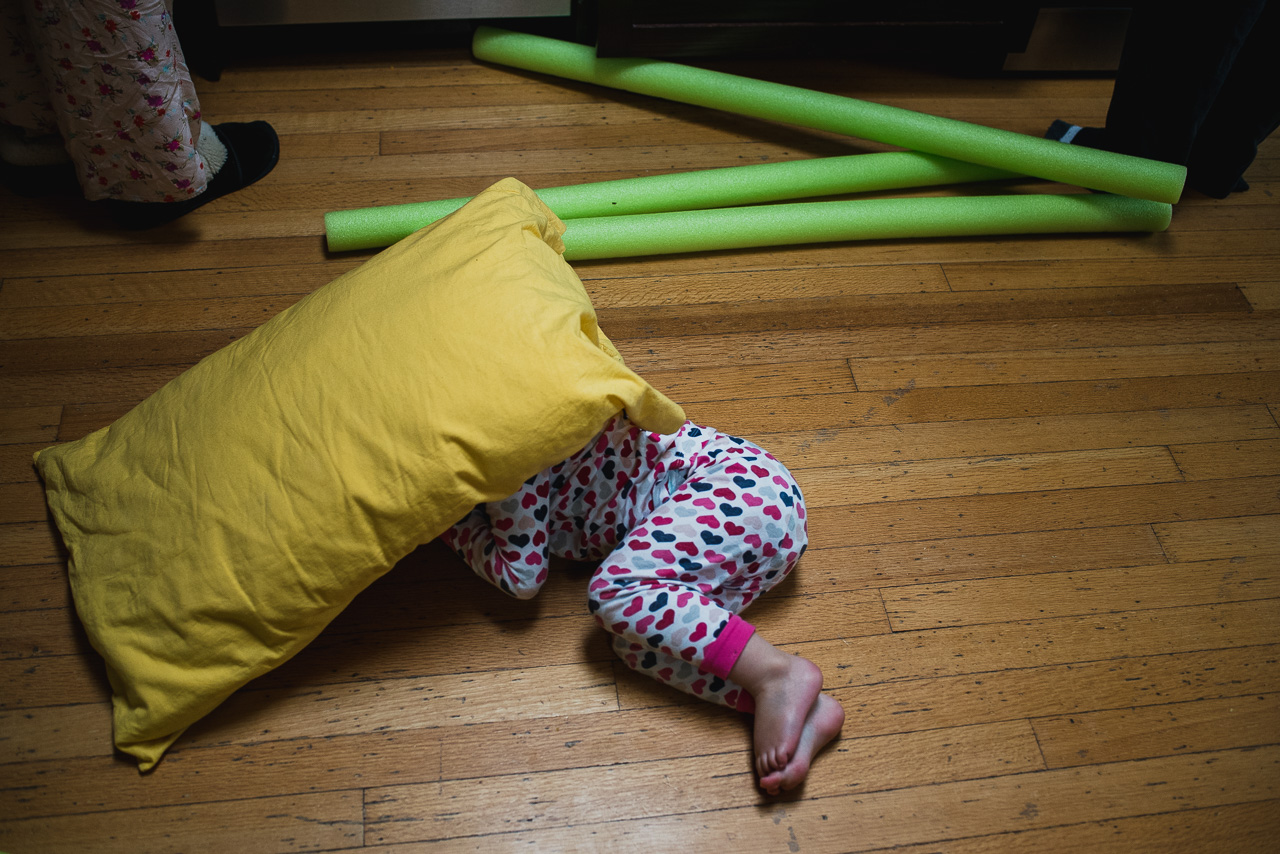 girl playing under pillow on kitchen floor