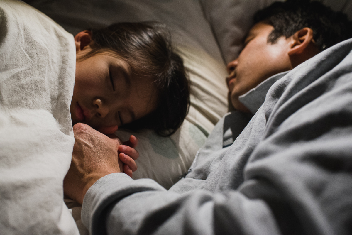 dad sleeping with daughter in bed.