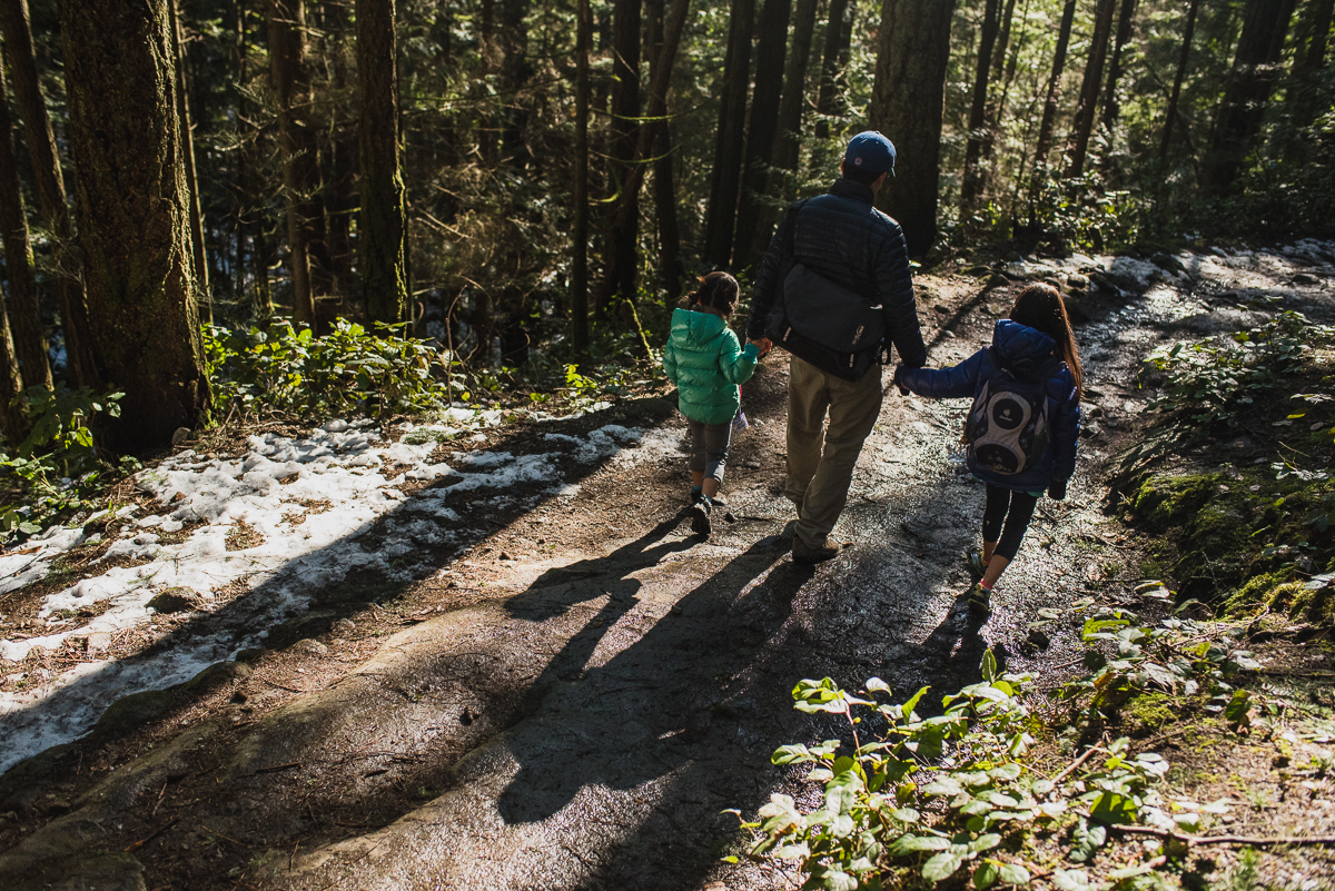 dad holding his daughters hands walking along a forest trail.