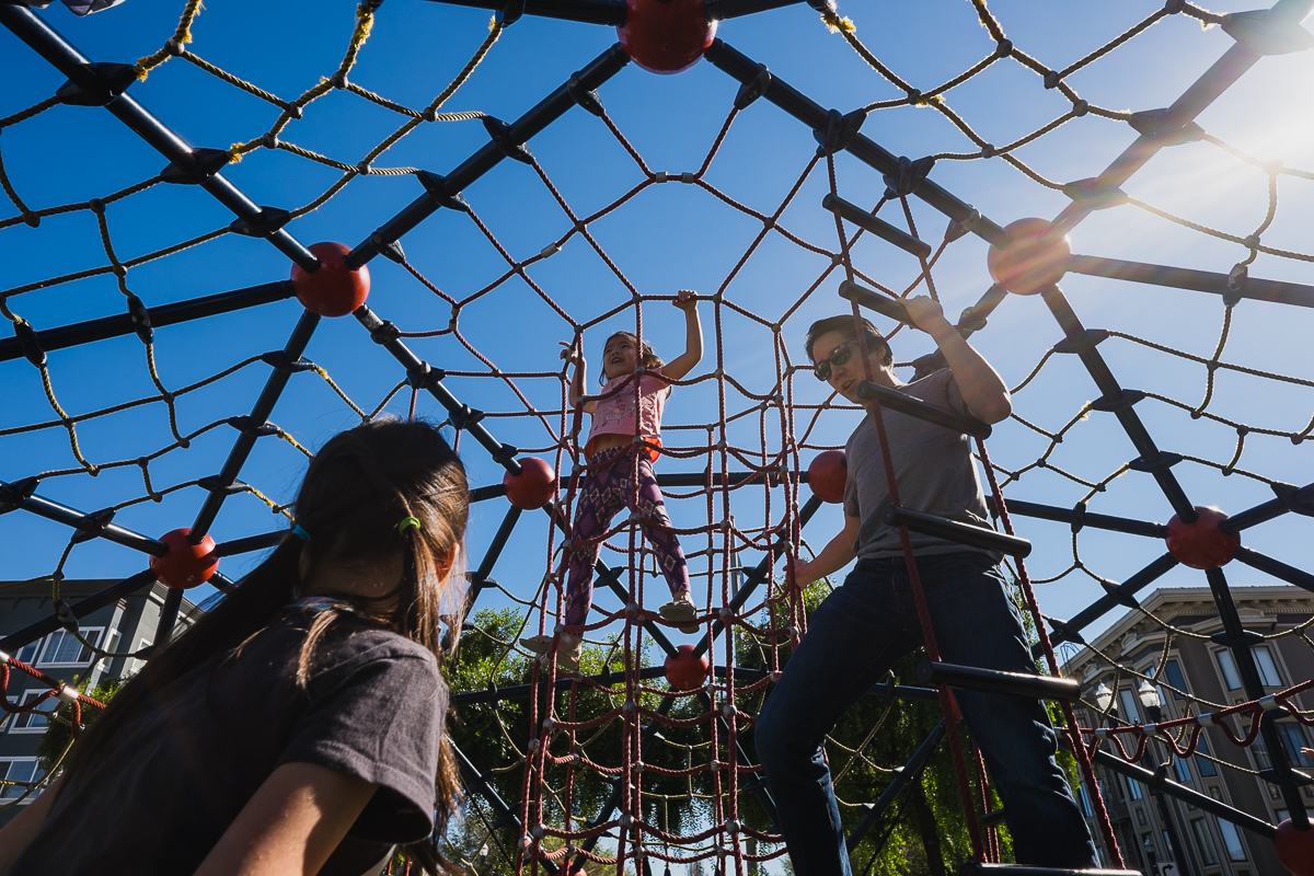 dad playing on playground climbing structure with girls