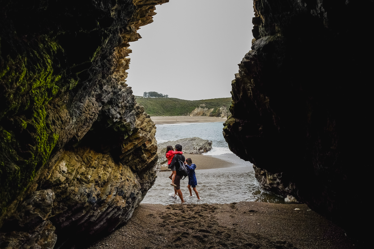 dad carrying daughters out of a cave before waves came.