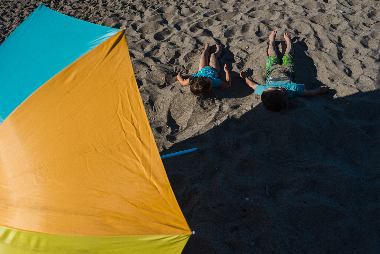 kids suntanning in the sand on a summer day at Spanish Banks