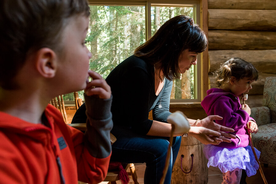 mom roasting marshmellows with kids at their mountain cabin