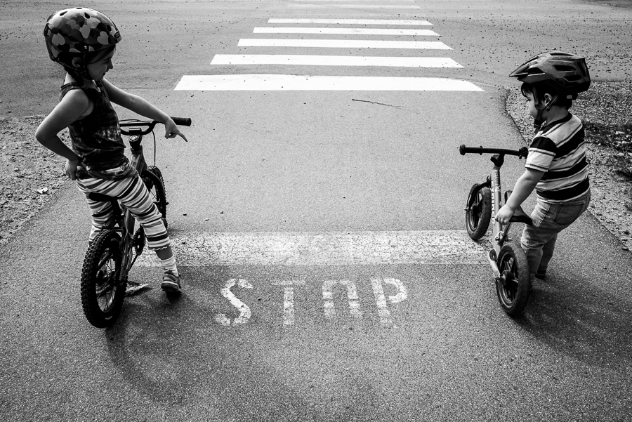 big sister telling brother to stop at the stop sign with his bike