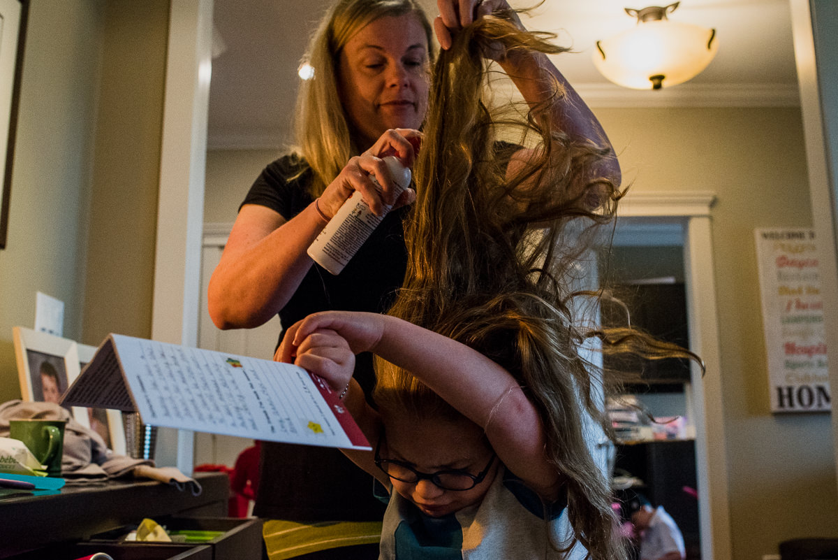 mom trying to do her daughter's hair while she resists
