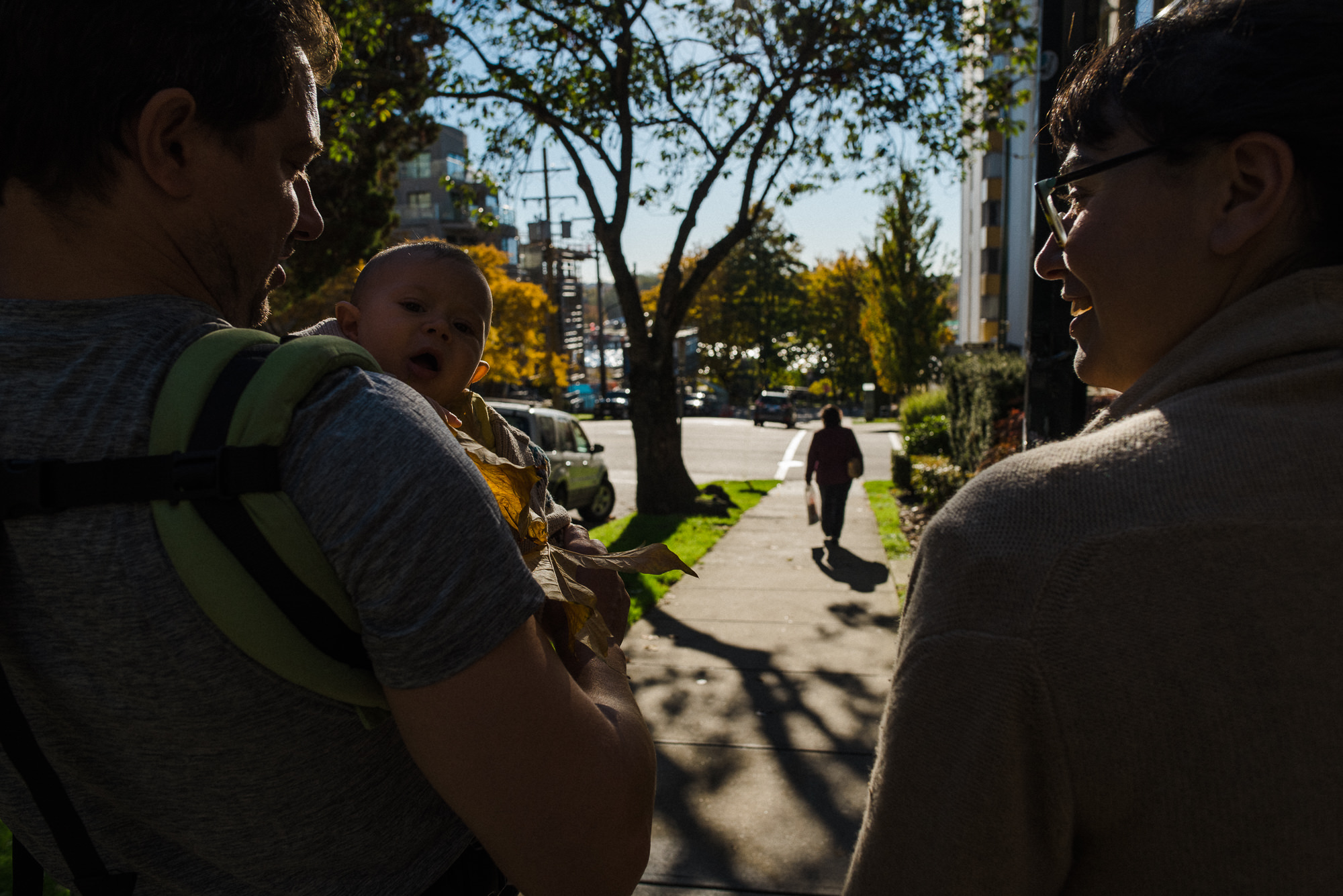 couple walking down the vancouver street while dad is wearing his baby in a carrier
