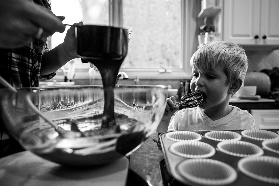 mom and son baking cupcakes and son licking baking paddles