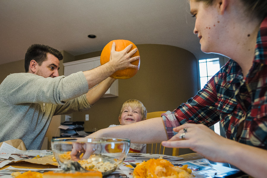 dad shaking out pumpkin guts over son's head