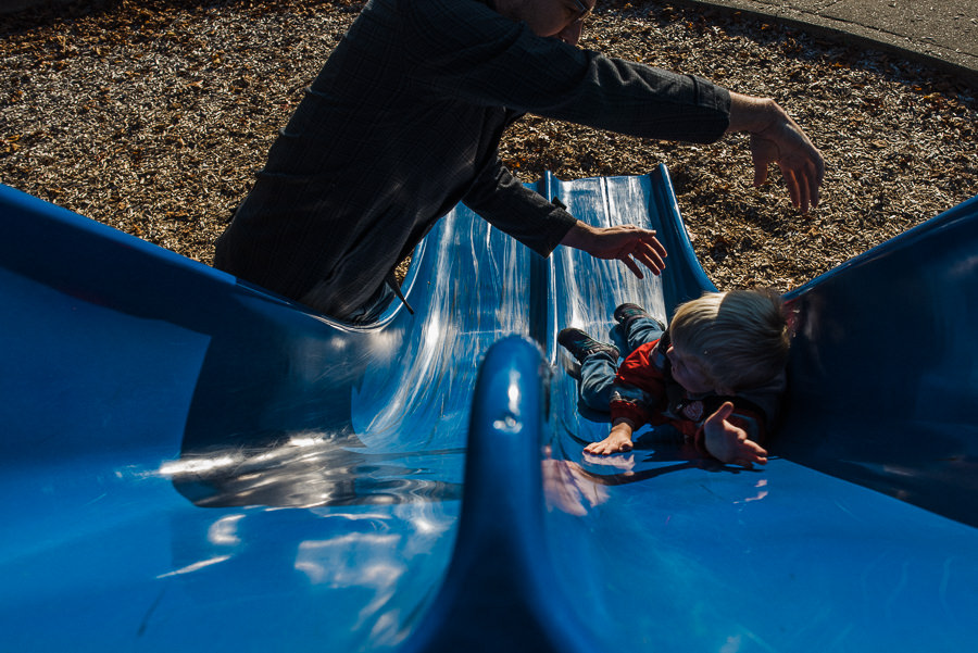 son slipping through dad's hands on slide