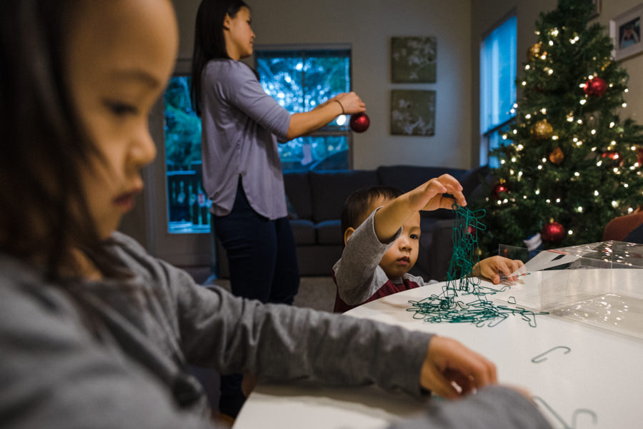 mom and kids decorating the christmas tree