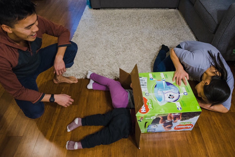 mom and dad playing with kids and cardboard box