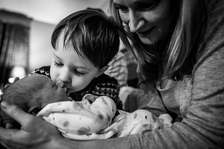 boy kissing his new baby brother while mom cuddles them both