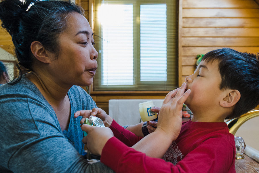 mom putting on lip balm on son's lips