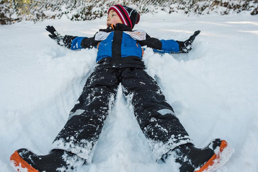 boy making snow angel