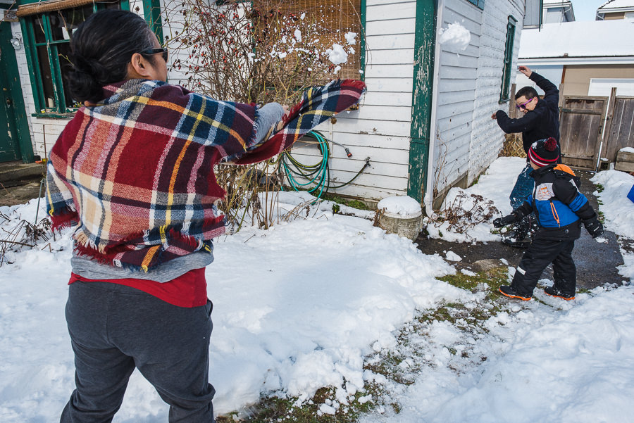 mom throwing snowball at dad and son