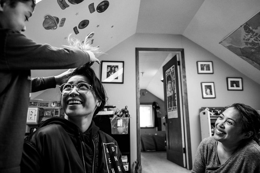 boy braiding his sister's hair while mom watches