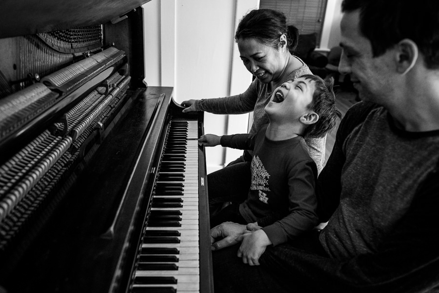 boy playing piano with parents