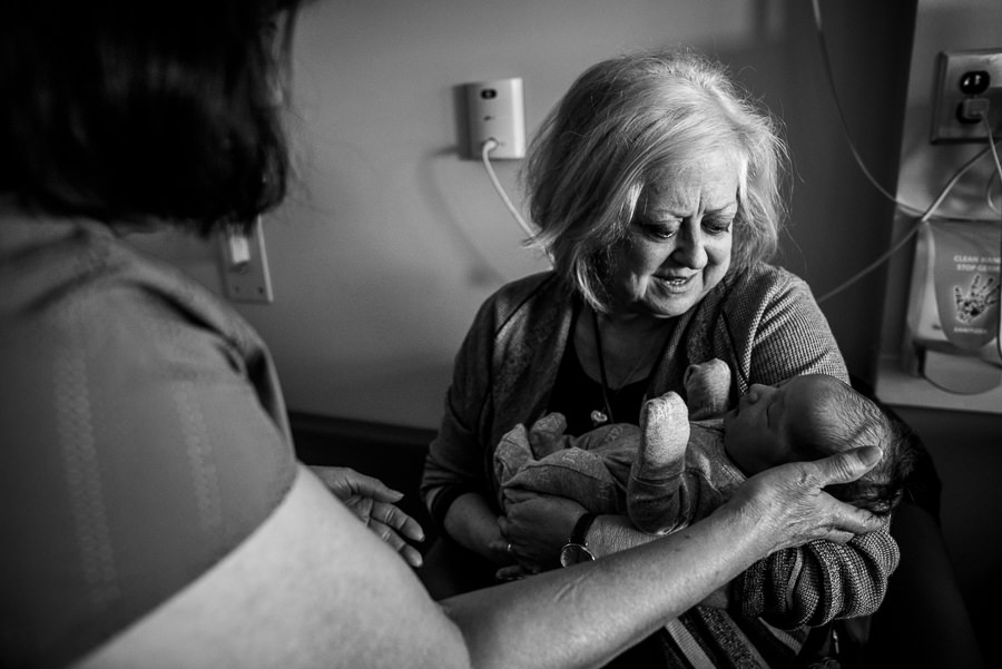 grandmothers holding their newborn baby grandson