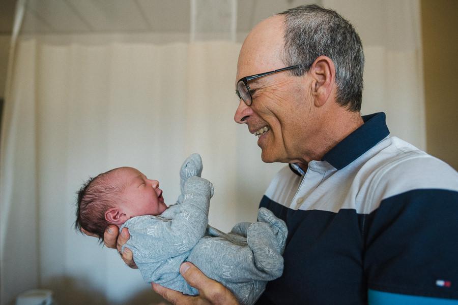 smiling grandfather holding newborn baby grandson