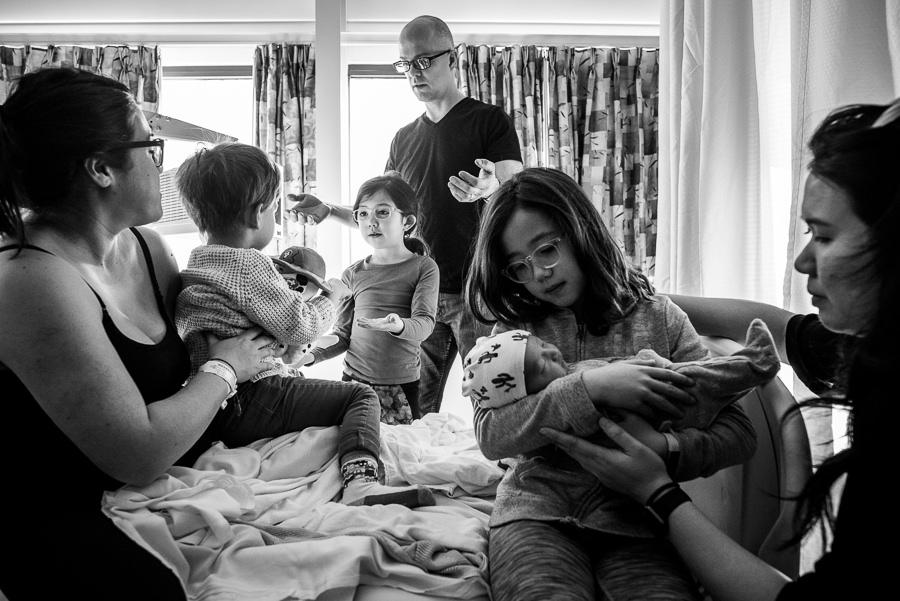 family visiting newborn baby boy in hospital maternity room