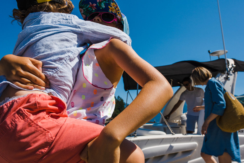 girl carrying her little brother while parents anchor the boat to the dock