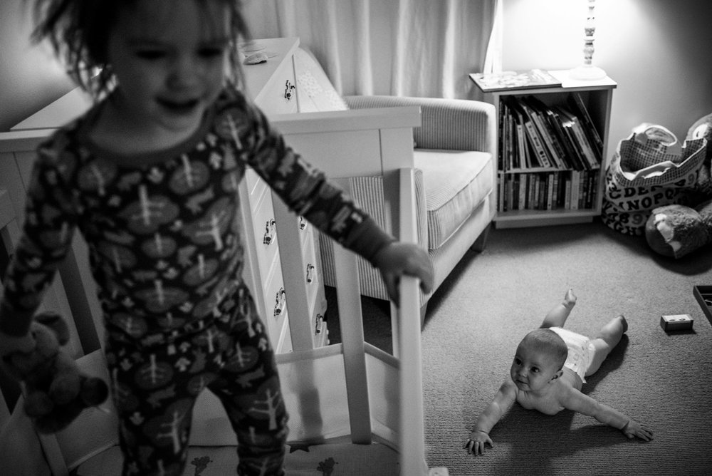 Big sister jumping in her crib while her baby sister watches her from the floor while lying on her tummy.