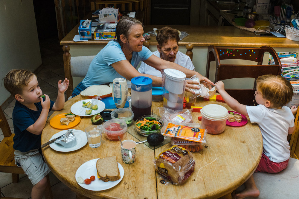 A family of three generations eats lunch together at the dining table.
