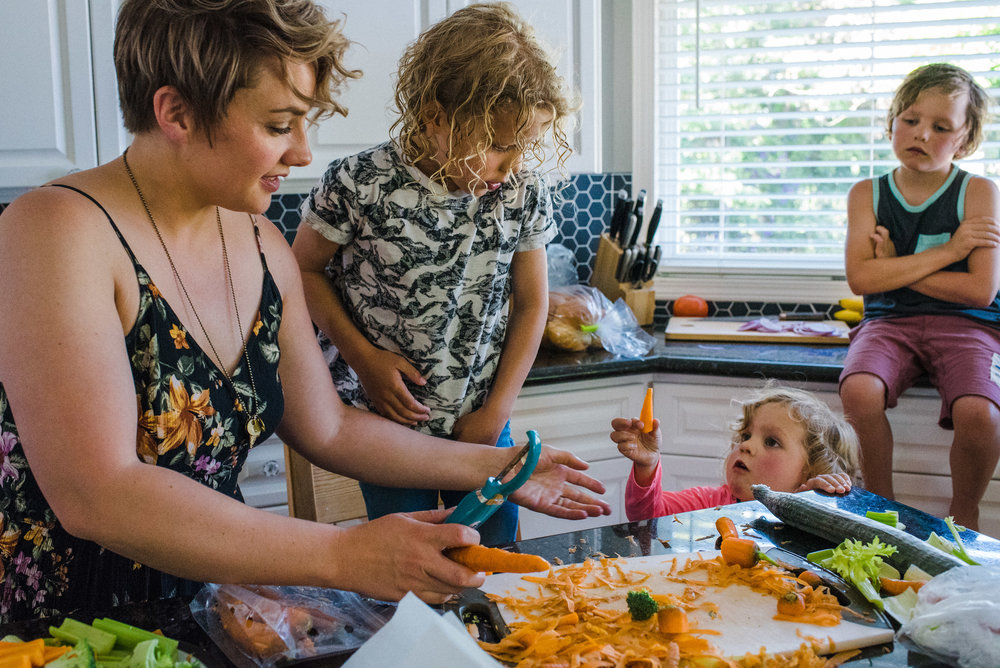 Three siblings helping their mom prepare dinner by grating carrots.