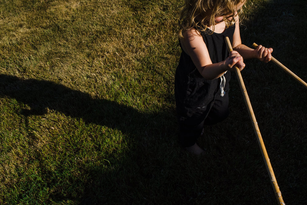 Little girl holding two wooden rods in the sun.