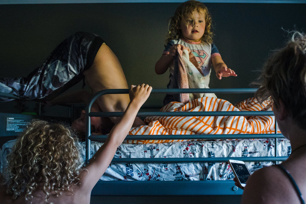 A mom checks the time on her phone while her kids are getting ready for bed.