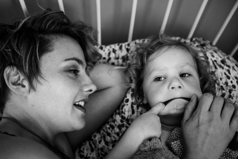 Mom lying in bed with her little girl who is making silly faces.