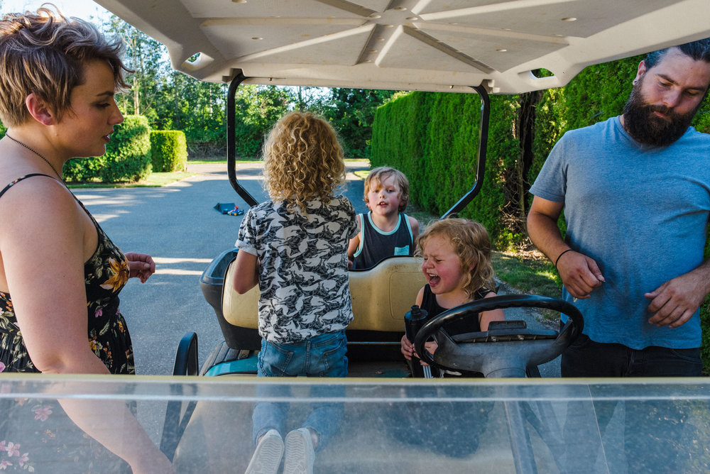 Little girl surrounded by her family is crying while sitting in the driver seat of a golf cart.