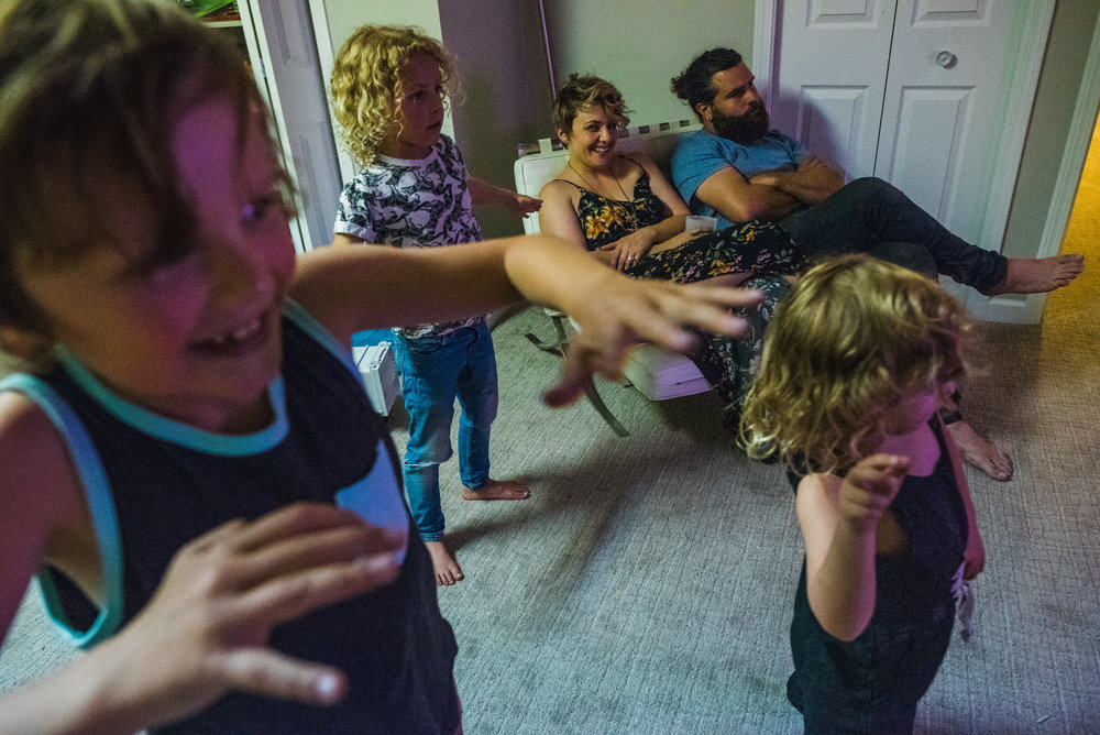 Kids playing Just Dance video game in the basement of their home while their parents watch their performance.