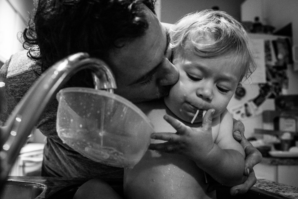 Dad kissing his son on the cheek while he eats spaghetti in the sink.