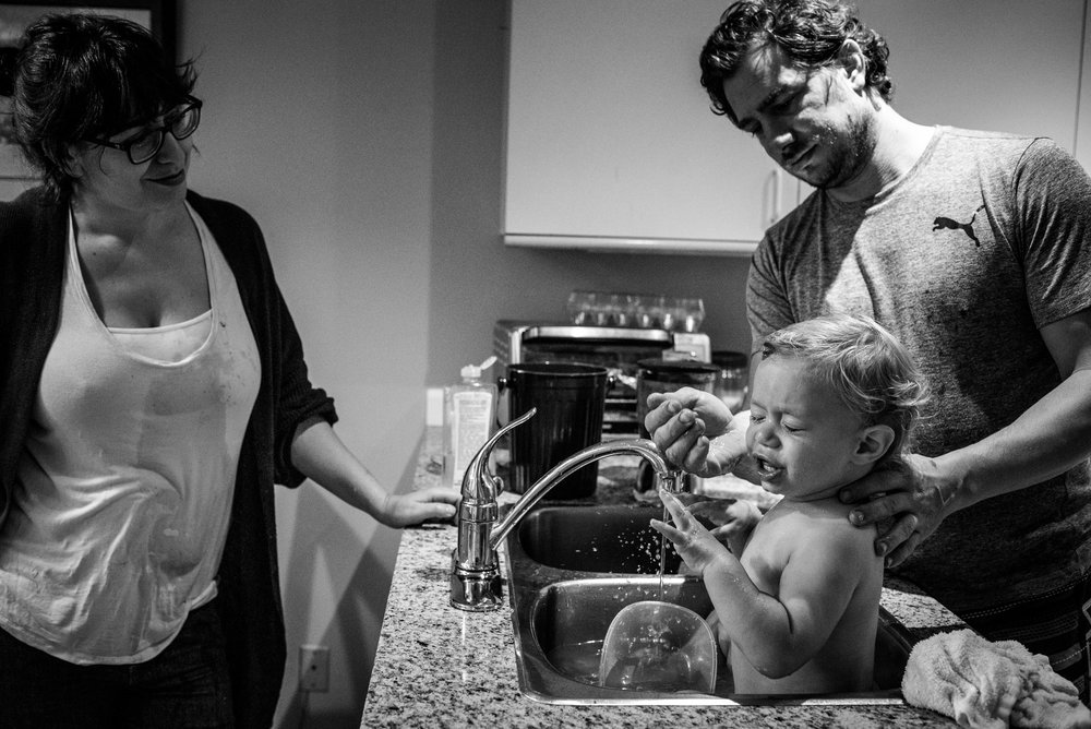 Dad washing food off his son's face while he is sitting in the sink.
