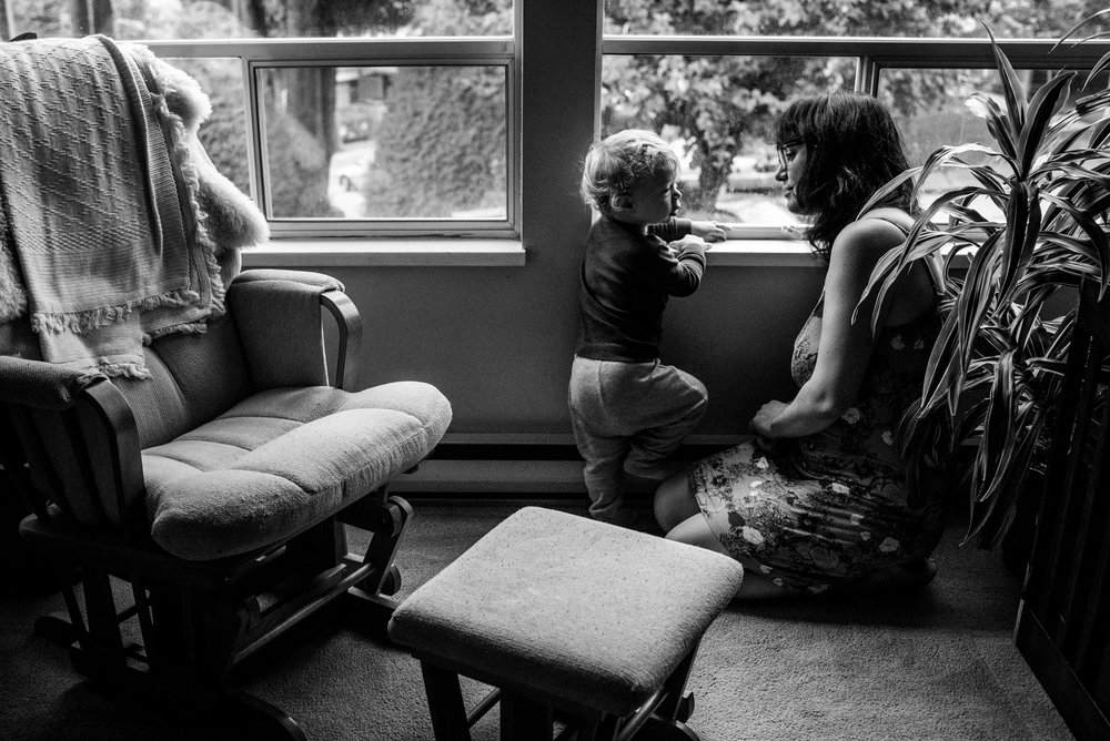 Mom and Toddler boy sharing a quiet moment by the living room window.