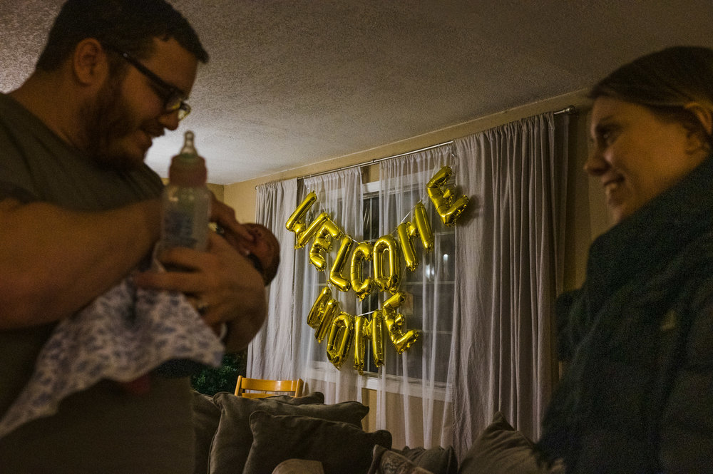 Welcome home balloons in the living room for newly adopted baby boy and his parents.