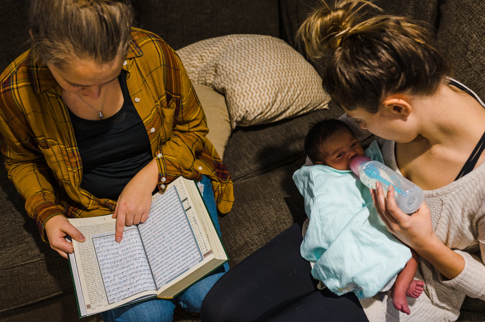 Mom reading Quran in English while Aunt feeds baby boy wiht a